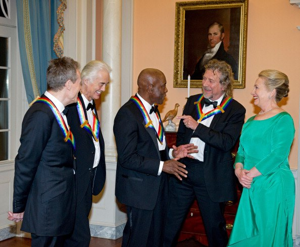 At a Dec. 1 State Department Dinner, Kennedy Center Honorees John Paul Jones, Jimmy Page, and robert Plant of Led Zeppelin joke around with blues guitar legend Buddy Guy as Secretary of State Hillary Clinton looks on.
